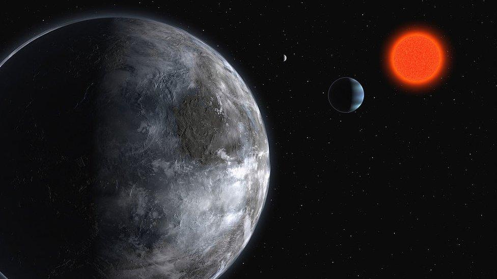 Representación de un planeta con una estrella enana roja.