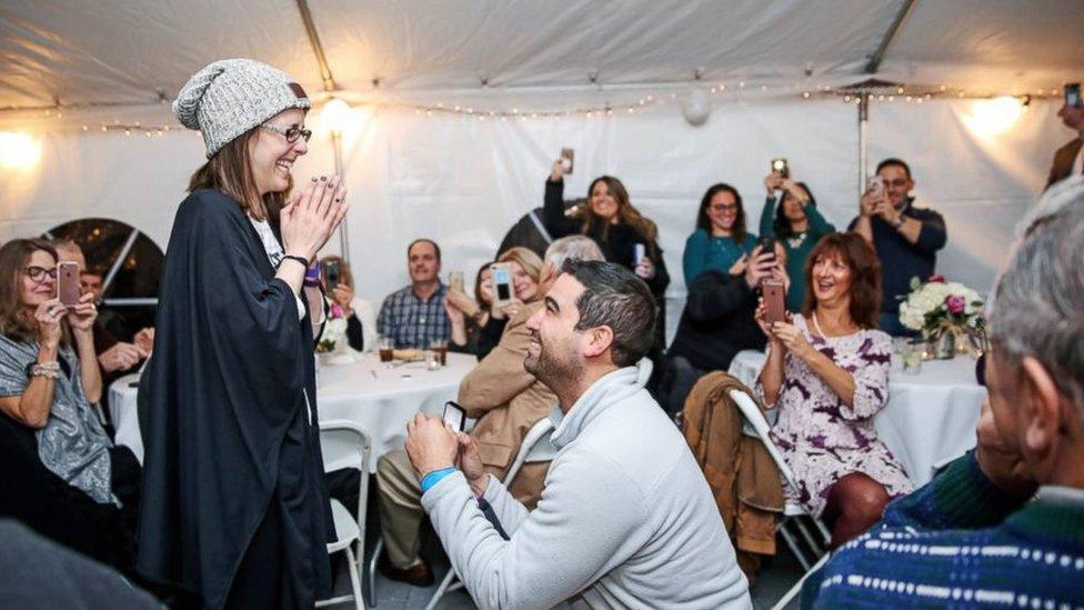 Danny, de rodillas, le propone matrimonio a Nicole, frente a sus amigos. Foto: Stephanie Scapellati.