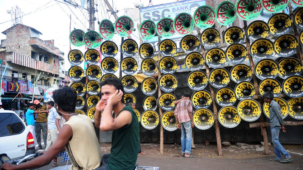 An Indian man protects his ears with his hands during a loudspeaker competition ahead of the Dussehra Hindu festival in Allahabad on September 20, 2015