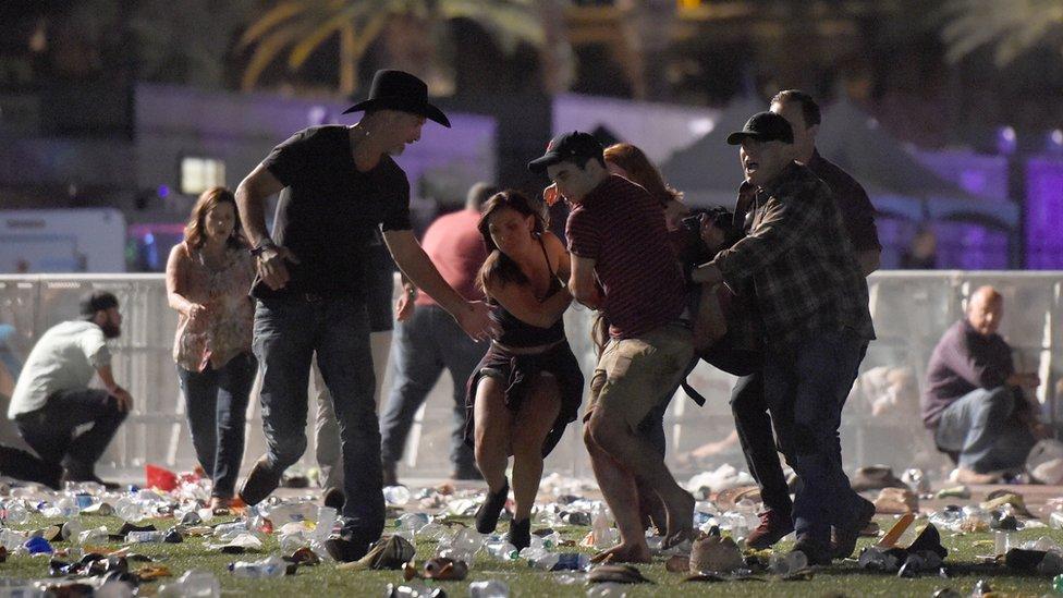 Un grupo de personas ayuda a una persona herida durante el tiroteo en Las Vegas