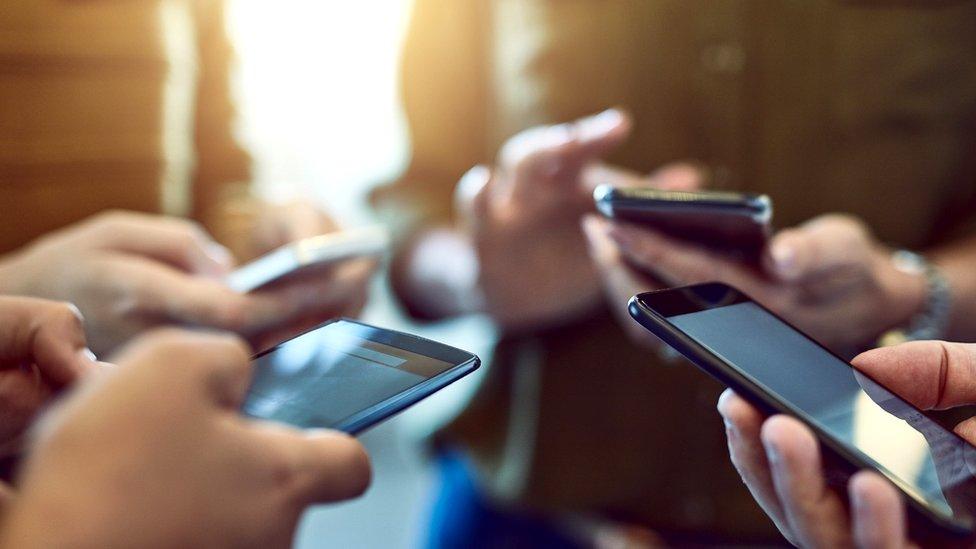 Grupo de gente con celulares.