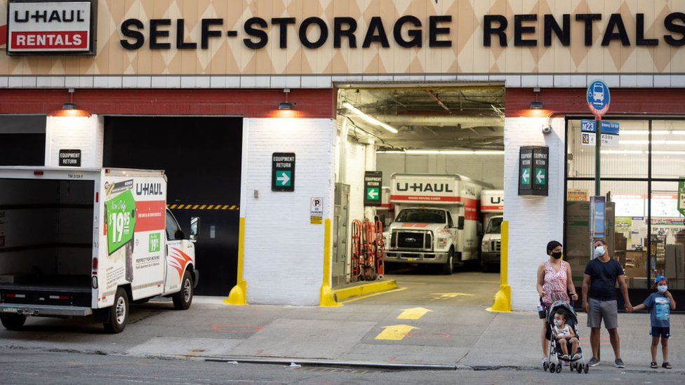 People wearing masks are seen standing outside a U-Haul rental depot on August 01, 2020 in New York City.