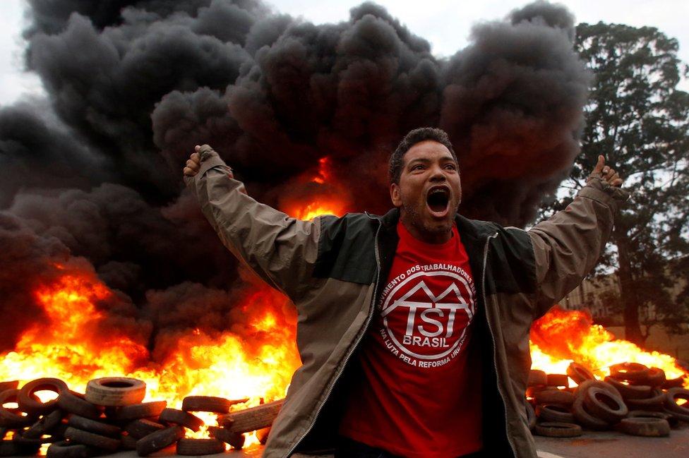 عضو في حركة العمال المشردين في البرازيل يرفع صوته احتجاجا على الرئيس البرازيلي، ميشيل تامر، في مدينة ساو باولو.