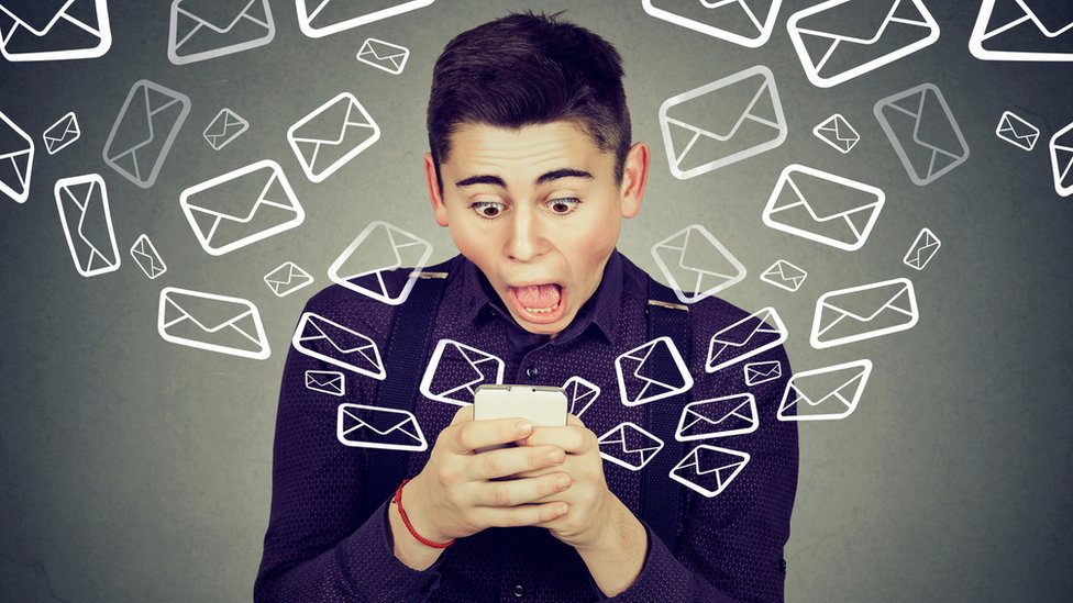 Un chico con su celular y cara de susto