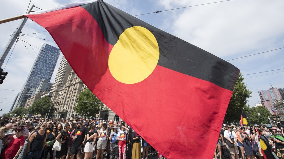 Protesters fly the Aboriginal flag over a march in Melbourne on Australia Day in 2019