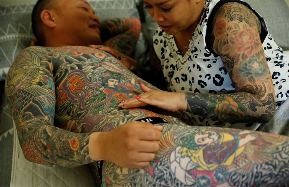 A woman with lots of tattoos touches a tattoo on the torso of her husband