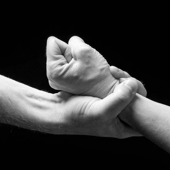 Un hombre le sujeta el puño a una mujer