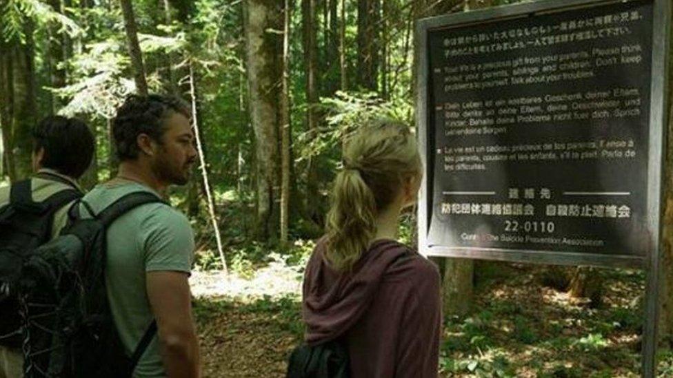 """Una escena de la película """"The Forest"""" muestra a los protagonistas frente a uno de los avisos dirigidos a los suicidas a la entrada del bosque, que existen en la vida real. (Foto: Gramercy Pictures)"""