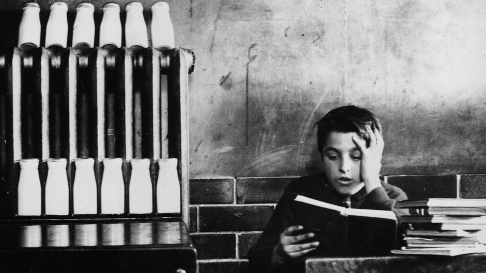 A schoolboy reads at his desk while a radiator takes the chill off the pupils' daily milk ration at an Ogmore Vale school, Glamorgan, in mid-winter, 1937