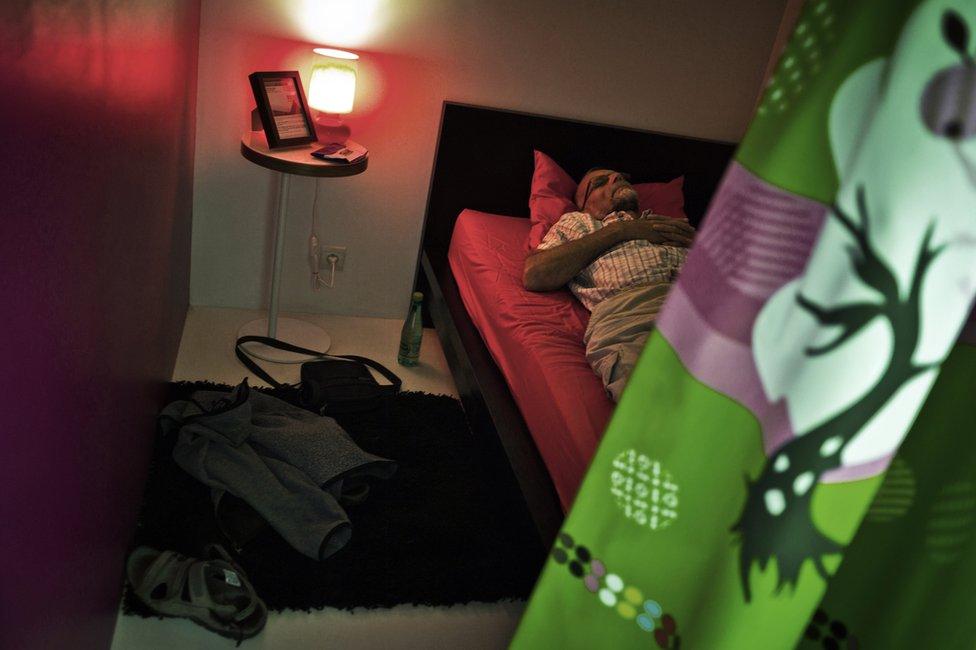 Hombre echándose una siesta en un local preparado para ello.