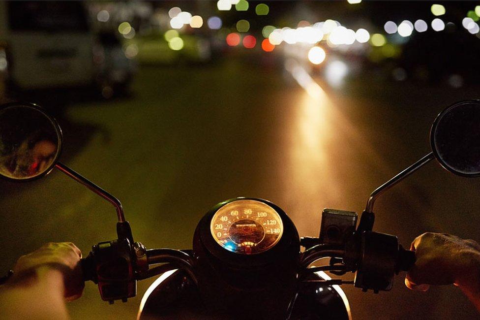 Motociclista circulando en la noche.