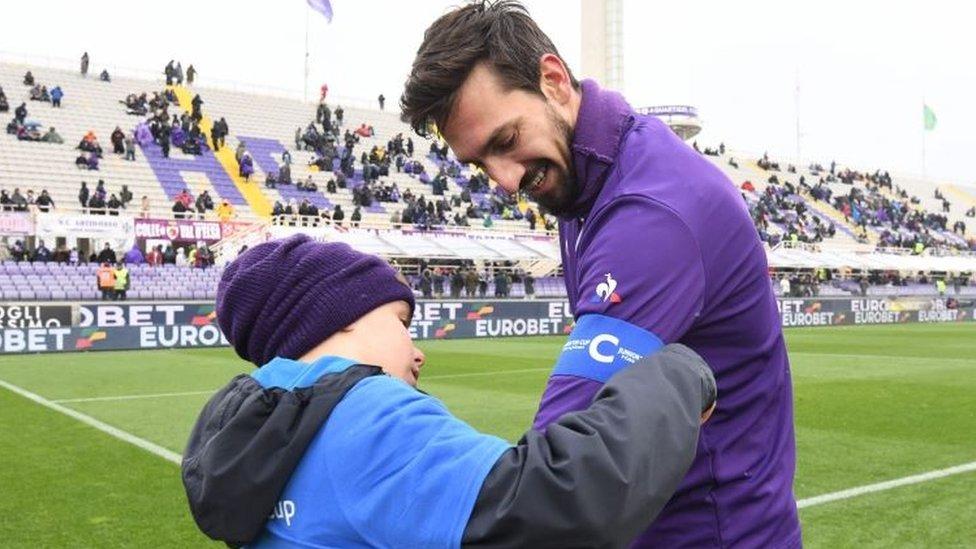 Davide Astori con un niño que le pone una banda