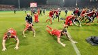 Wales team slide along the pitch in celebration