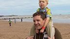 Man with son on Clacton beach