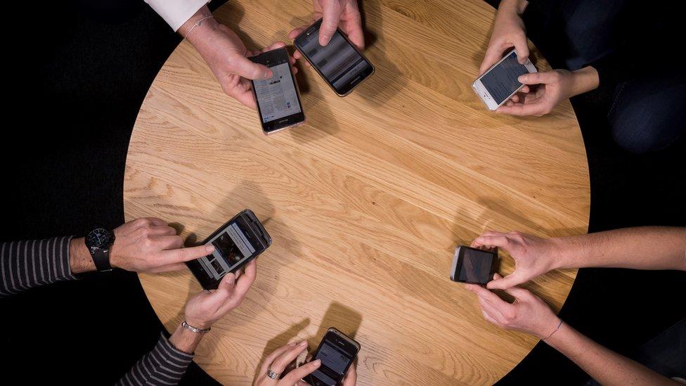 Personas con teléfonos celulares