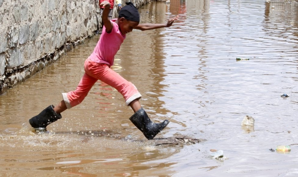 A child jumps through floodwaters near houses.