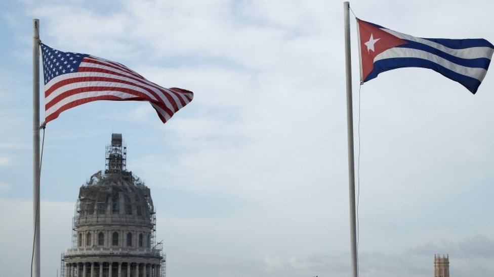 US and Cuban flags fly side-by-side on the roof of the Iberostar Hotel Parque Central near El Capitolio (background) in the historic Old Havana neighborhood (20 March 2016)