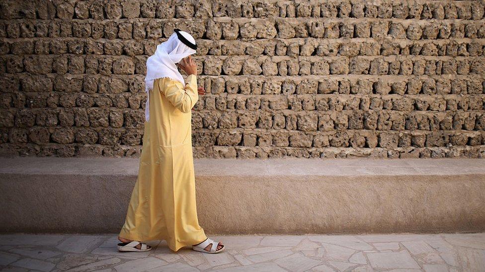 Un hombre habla en su teléfono móvil mientras camina por el Dubai Heritage Village el 13 de noviembre de 2013 en Dubai, Emiratos Árabes Unidos.