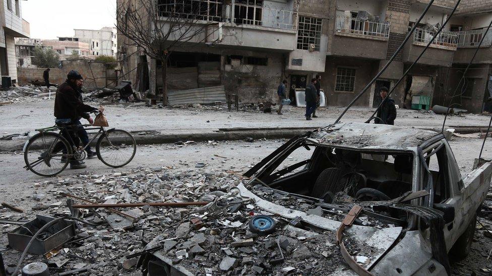 رجال وسط آثار القصف الجوي في الغوطة الشرقية