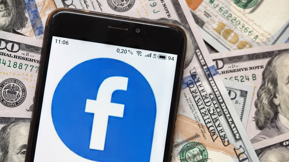 Facebook logo on phone with dollar bills in background