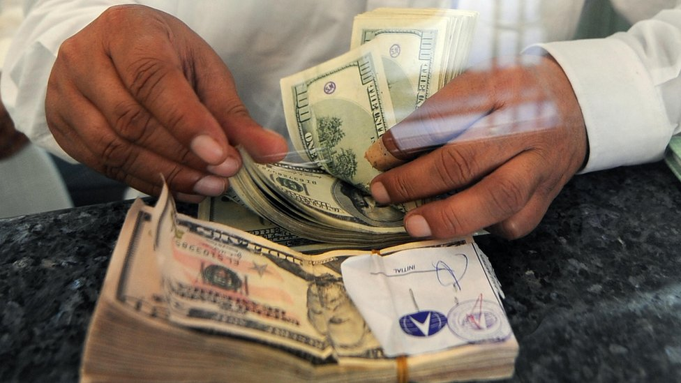 Un hombre con un fajo de dólares en la mano.