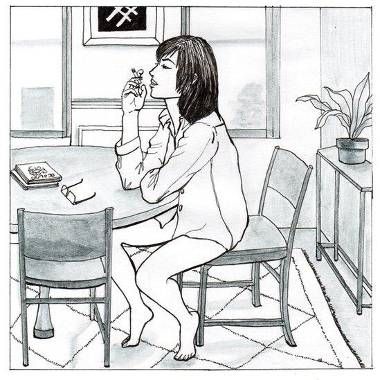 Mujer fumando en la cocina en camisa.