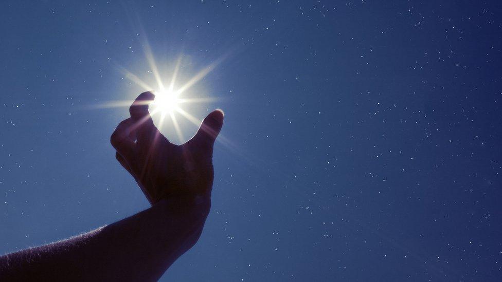 Mano alzada hacia el Sol