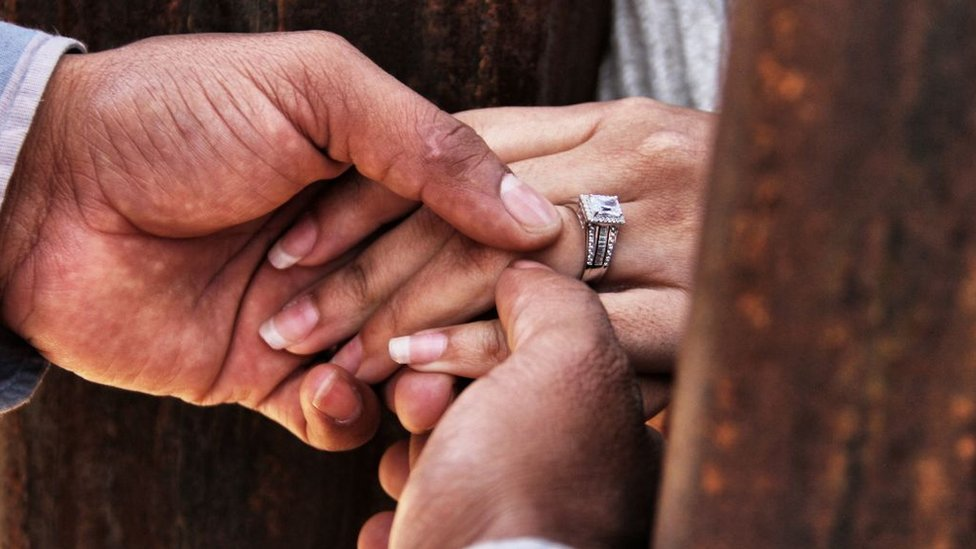 Un hombre coloca una alianza en el dedo de su prometida.