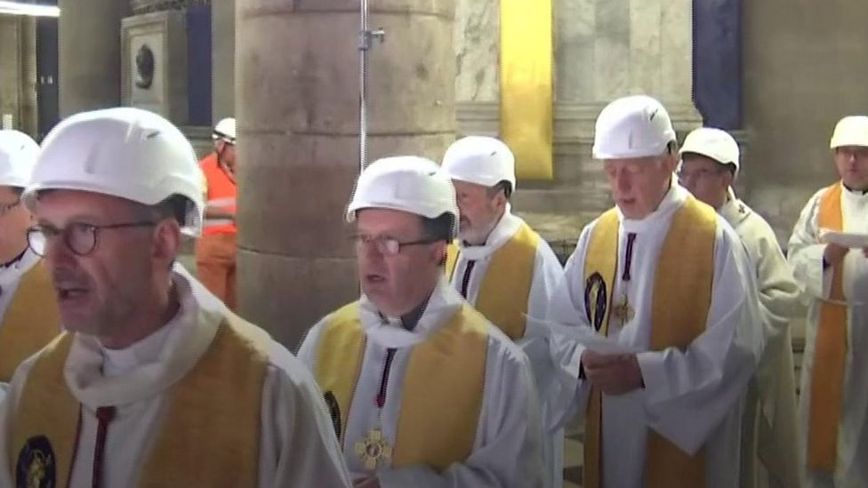 Priests wear hard hats at Notre-Dame