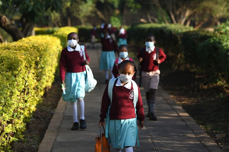 Children wearing masks and uniforms return to their primary school in Nairobi.