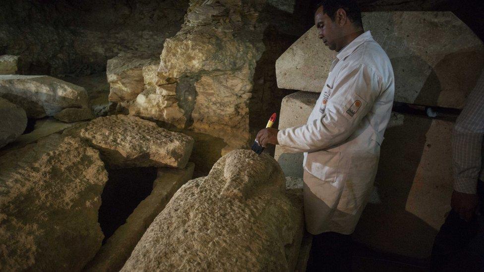 Un arqueólogo egipcio trabaja en un sarcófago en la reciente necrópolis descubierta.