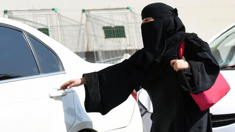 Una mujer saudí aborda un auto en la parte trasera