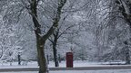 Snow covered parkland. A red telephone box can be seen in the middle of the photo