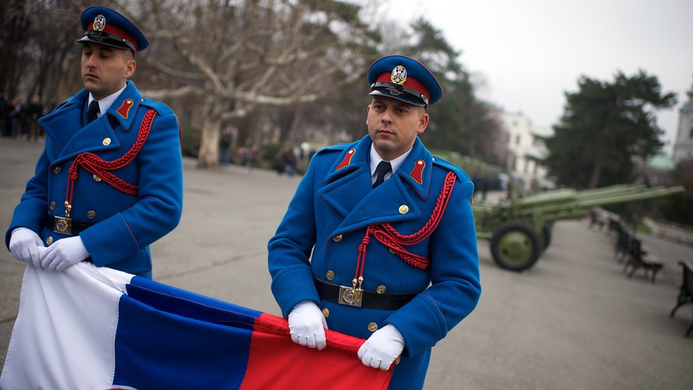 Soldiers hold the national flag as part of Serbia's Statehood Day celebrations