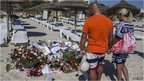 Tourists pay their respects in front of a makeshift memorial at the beach near the Imperial Marhaba resort, which was attacked by a gunman in Sousse, Tunisia, June 29, 2015.