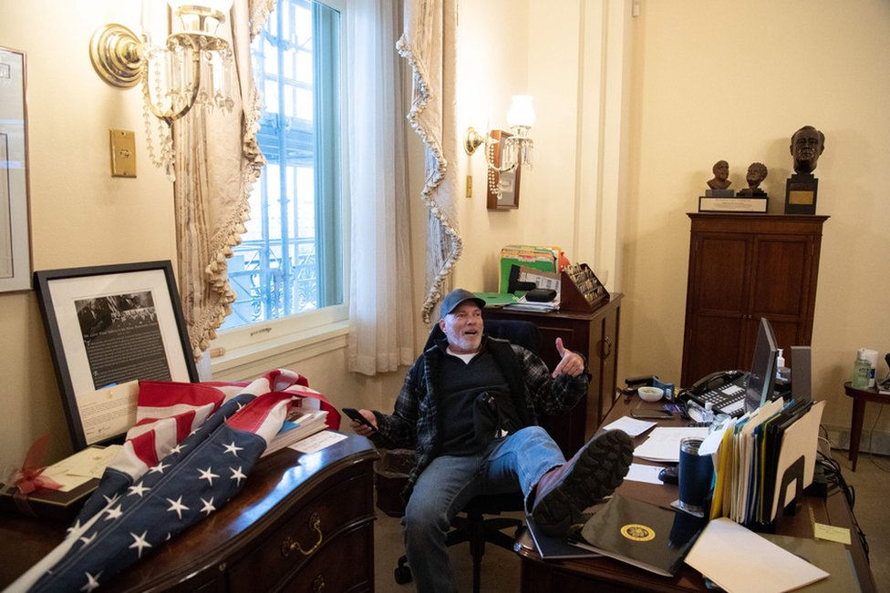 Richard Barnett, a supporter of President Donald Trump sits inside the office of Speaker of the House Nancy Pelosi as he protest inside the US Capitol in Washington, DC, 6 January 2021.