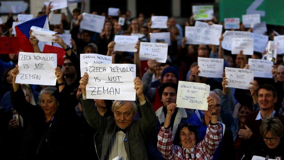 Manifestantes sostienen pancartas durante una protesta en octubre para exigir la renuncia del presidente Zeman.