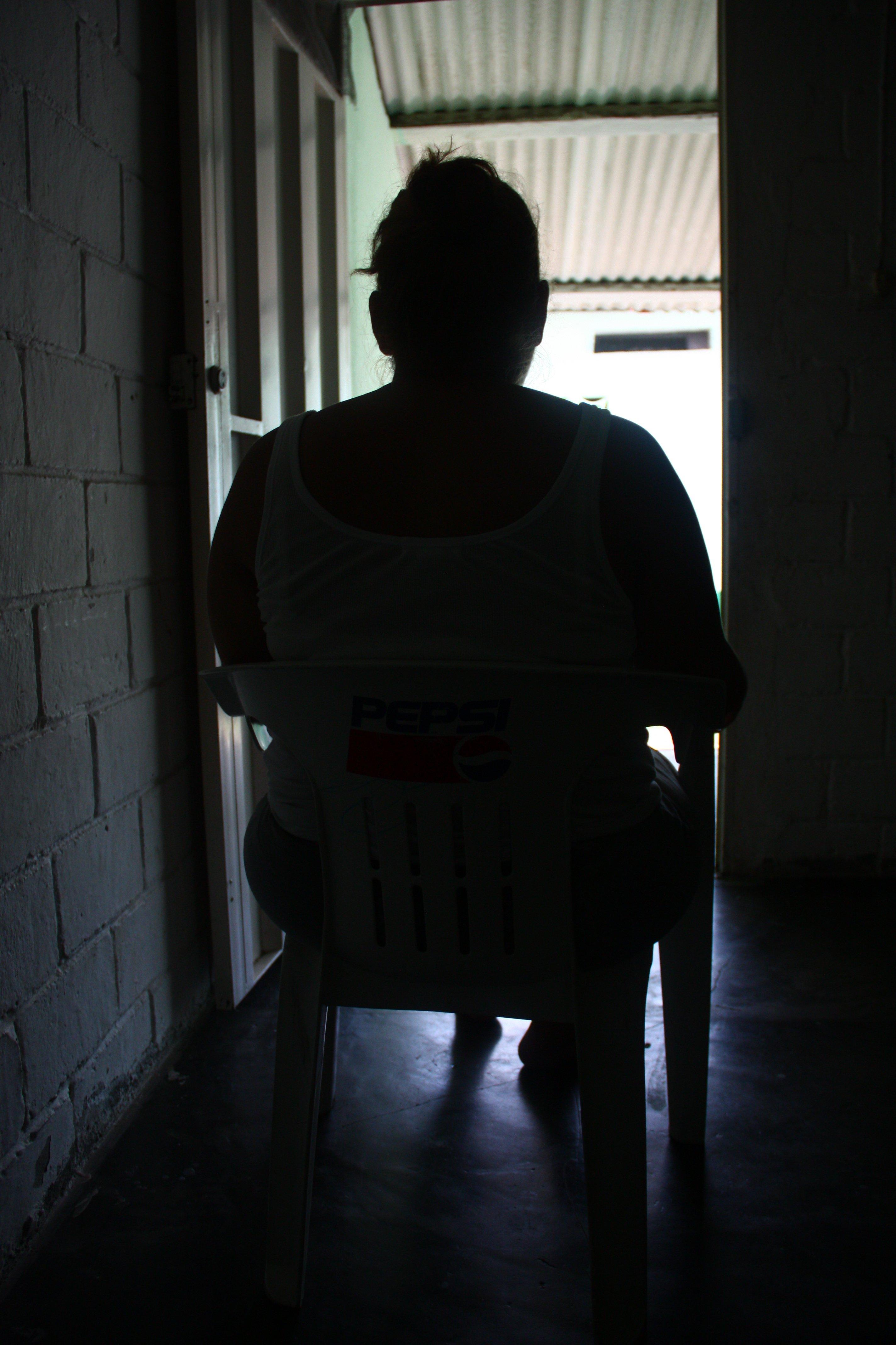 María de espaldas en el cuarto en el que vivía con sus hijos a la espera de ser reubicados en México. (Foto: Leire Ventas)
