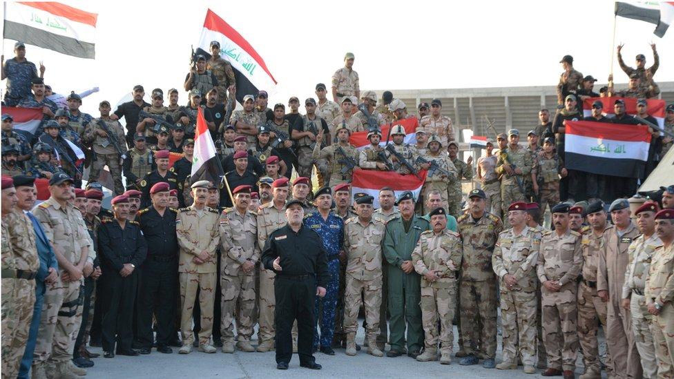 الرئيس العراقي حيدر العبادي رافعاً العلم العارقي بعد اعلان النصر في الموصل