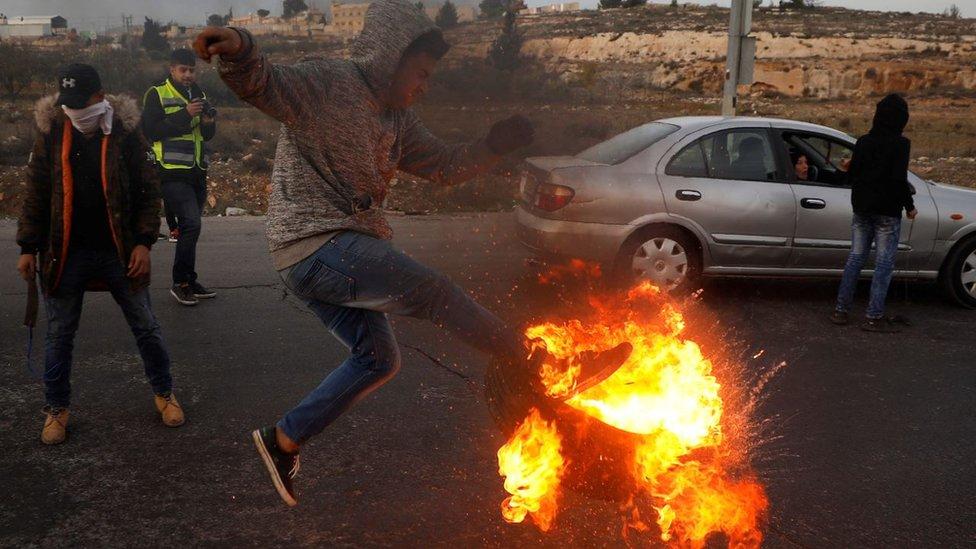 Un joven con un neumático en llamas