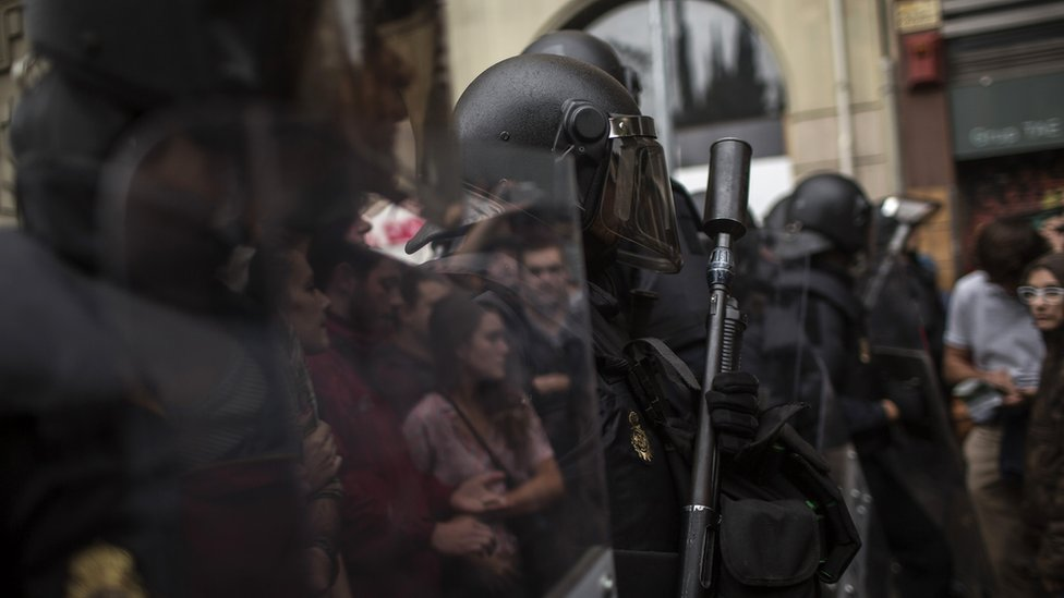 Protesters are reflected on the shields of Spanish police officers outside the Ramon Llull polling station in Barcelona October 1, 2017 during a referendum on independence for Catalonia banned by Madrid.