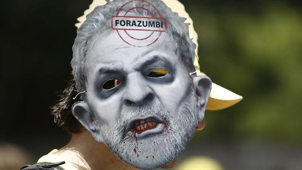 Un manifestante con una máscara contra Lula.