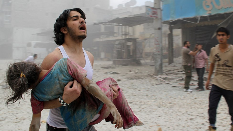 Man holds injured woman in Aleppo