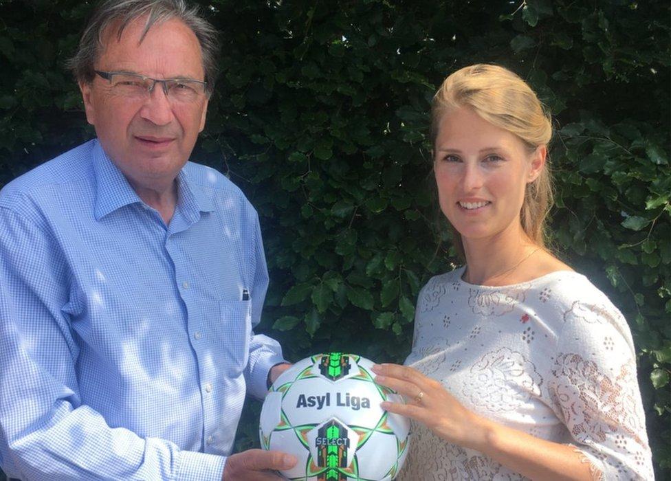 Per Bjerregaard holding an Asylum League football with Danish Red Cross President Hanna Line Jakobsen