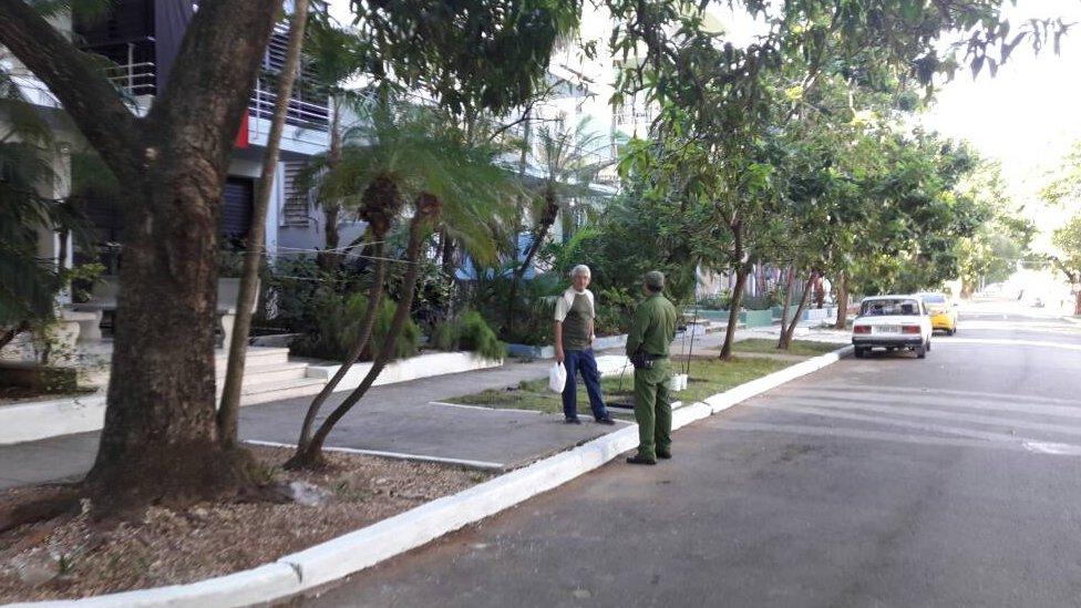Un guardia vestido de verde en la calle.