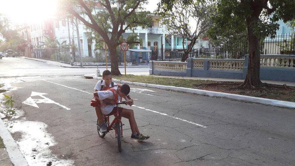 Dos niños paseando en una bicicleta.