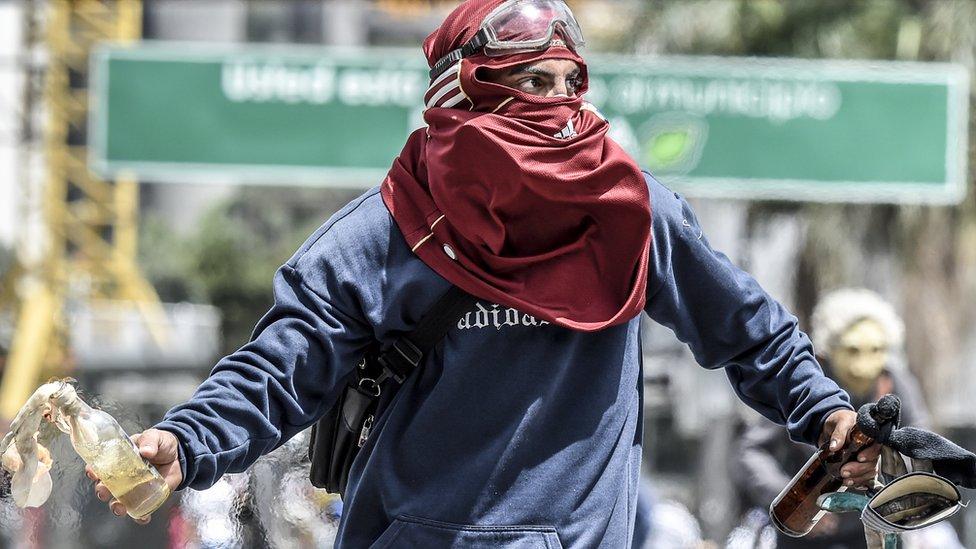 Un manifestante con un cóctel molotov.