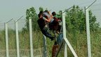 Afghan men breach the fence at Hungary's border