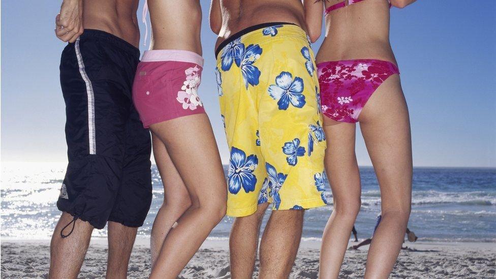Chicos y chicas en bañador y bikini en la playa