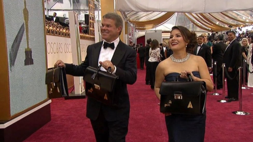 Martha Ruiz y Brian Cullinan, en la alfombra roja, con las maletas en las que cargan los sobres con los nombres de los ganadores.